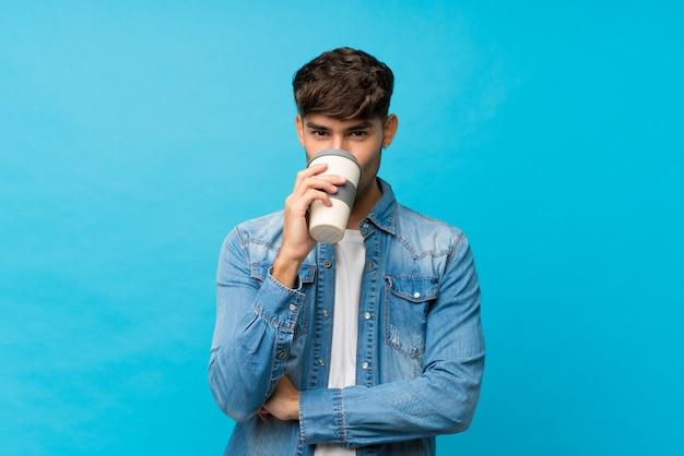 Młody przystojny mężczyzna trzyma kawę i pije zabrać