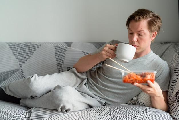 Młody przystojny mężczyzna trzyma kimchi i picia kawy w domu