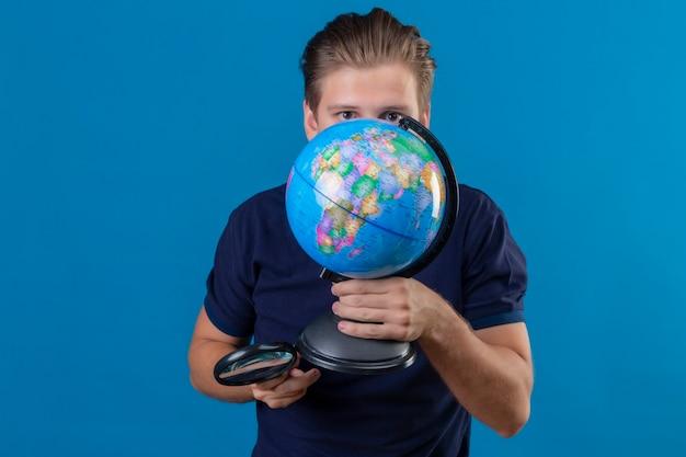 Młody przystojny mężczyzna trzyma kulę ziemską i szkło powiększające, chowając się za kulą ziemską stojąc na niebieskim tle