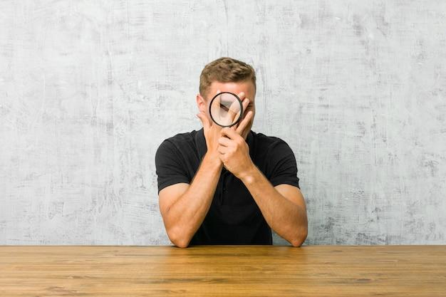 Młody przystojny mężczyzna trzyma lupę mruga przez palce przestraszony i zdenerwowany.