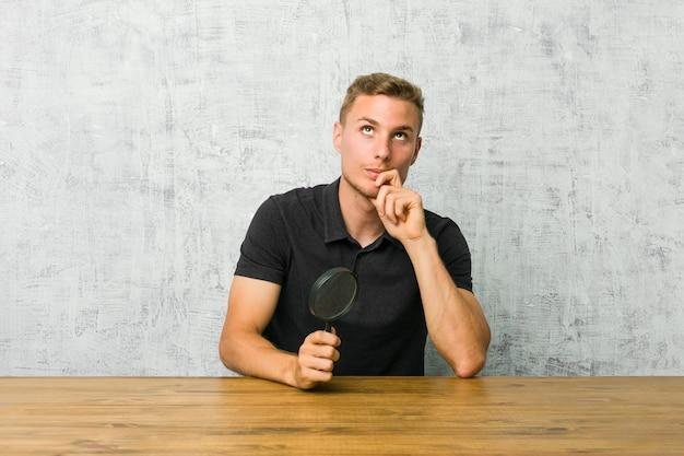 Młody przystojny mężczyzna trzyma lupę patrząc z ukosa z wyrazem wątpliwości i sceptycyzmu.