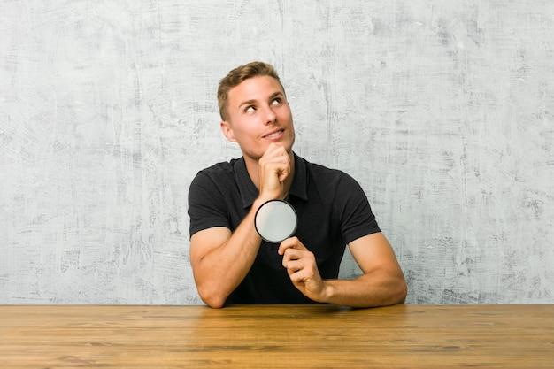 Młody przystojny mężczyzna trzyma lupę patrzeje z ukosa z wątpliwym i sceptycznym wyrażeniem