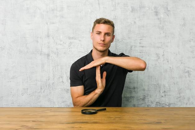 Młody przystojny mężczyzna trzyma lupę pokazujący gest limitu czasu.