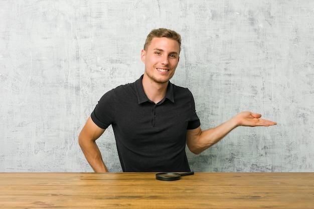 Młody przystojny mężczyzna trzyma lupę pokazuje odbitkową przestrzeń na dłoni i trzyma inną rękę na talii.