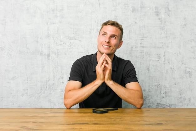 Młody przystojny mężczyzna trzyma lupę tworzących plan na myśli, ustanawiając pomysł