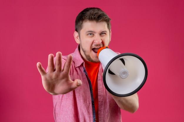 Młody przystojny mężczyzna trzyma megafon, krzycząc do niego, robiąc znak stopu ręką