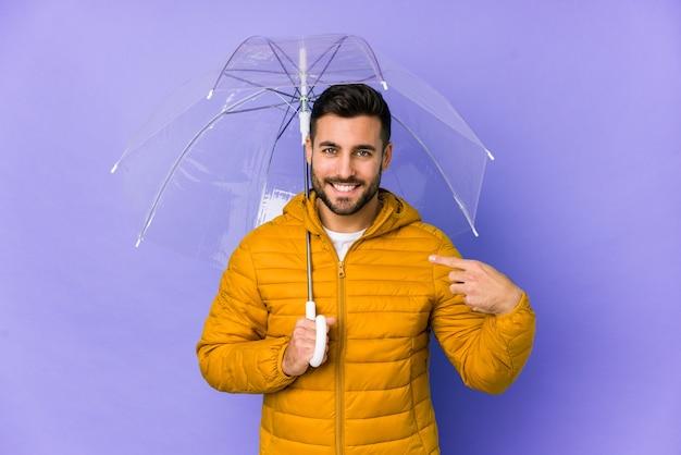 Młody przystojny mężczyzna trzyma parasol na białym tle osoba, wskazując ręką na przestrzeni kopii koszuli, dumny i pewny siebie