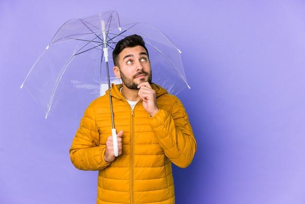 Młody przystojny mężczyzna trzyma parasol na białym tle patrząc z ukosa z wątpliwym i sceptycznym wyrazem twarzy.