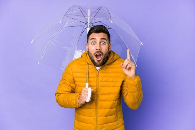 Młody przystojny mężczyzna trzyma parasol na białym tle pomysł, koncepcja inspiracji.