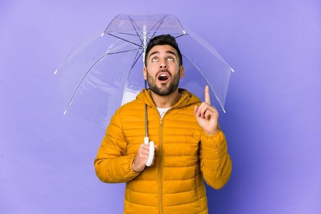 Młody przystojny mężczyzna trzyma parasol na białym tle, wskazując do góry z otwartymi ustami.