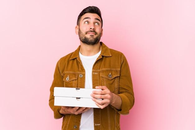 Młody przystojny mężczyzna trzyma pizze na białym tle marzy o osiągnięciu celów i zamierzeń
