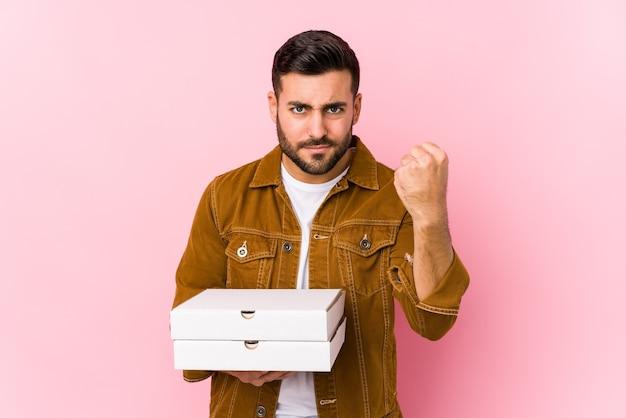 Młody przystojny mężczyzna trzyma pizze na białym tle wyświetlono pięść, agresywny wyraz twarzy.