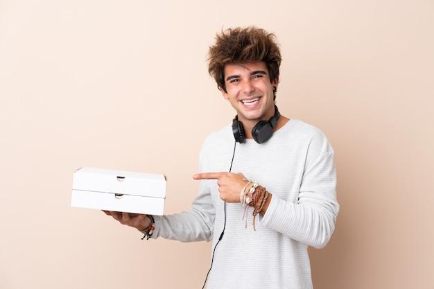 Młody przystojny mężczyzna trzyma pizzę nad odosobnioną ścianą i wskazuje je