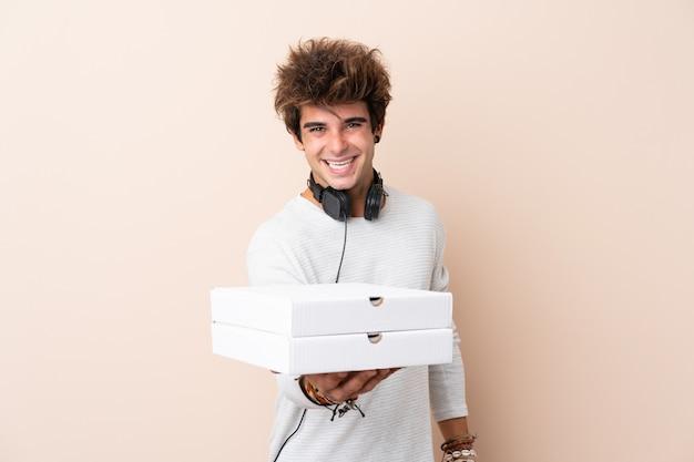 Młody przystojny mężczyzna trzyma pizzę nad odosobnioną ścianą z szczęśliwym wyrażeniem
