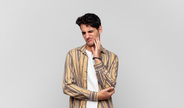 Młody przystojny mężczyzna trzyma policzek i cierpi na bolesny ból zęba, czuje się chory, nieszczęśliwy i nieszczęśliwy, szuka dentysty