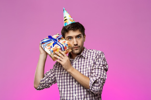 Młody przystojny mężczyzna trzyma prezent urodzinowy nad purpury ścianą.