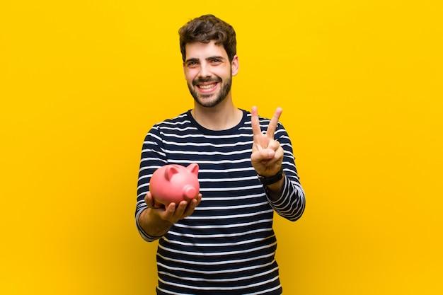 Młody przystojny mężczyzna trzyma prosiątko banka pomarańcze backgroun