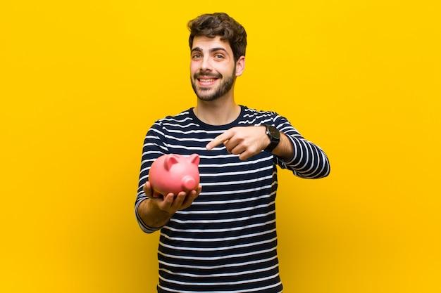 Młody przystojny mężczyzna trzyma prosiątko banka przeciw pomarańczowemu backgroun