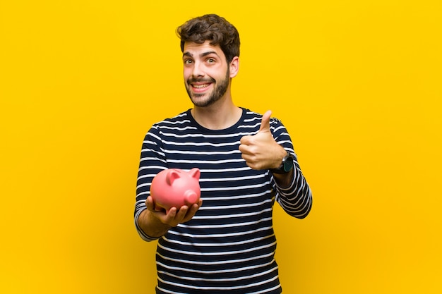 Młody przystojny mężczyzna trzyma prosiątko banka
