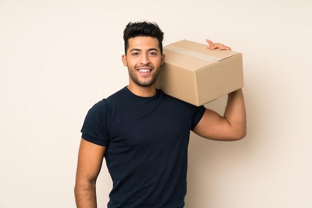 Młody przystojny mężczyzna trzyma pudełko, aby przenieść go do innej witryny