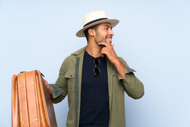 Młody przystojny mężczyzna trzyma rocznik teczkę nad odosobnioną błękit ścianą myśleć pomysł i patrzeje stronę