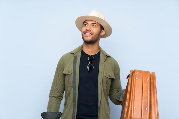 Młody przystojny mężczyzna trzyma rocznik teczkę nad odosobnioną błękit ścianą przyglądającą up podczas gdy ono uśmiecha się