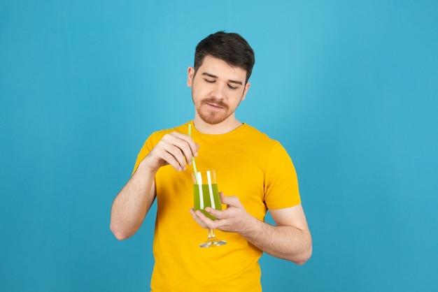 Młody przystojny mężczyzna trzyma świeży koktajl i mieszanie go.