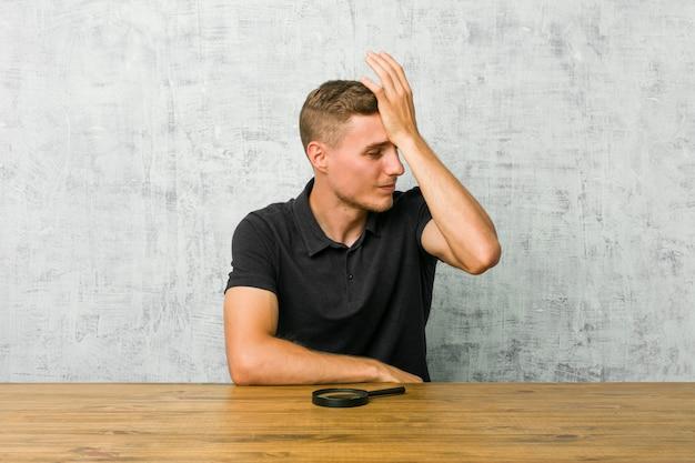 Młody przystojny mężczyzna trzyma szkło powiększające, zapominając o czymś, uderzając dłonią w czoło i zamykając oczy.