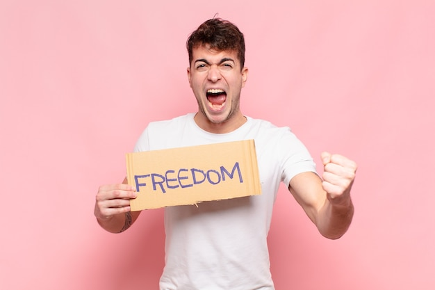 Młody przystojny mężczyzna trzyma tablicę wolności