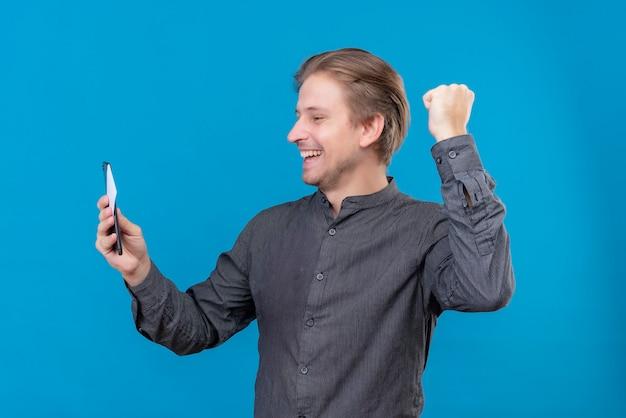 Młody przystojny mężczyzna trzyma telefon komórkowy