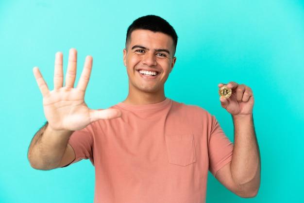Młody przystojny mężczyzna trzymający bitcoina na odosobnionym niebieskim tle, licząc pięć palcami