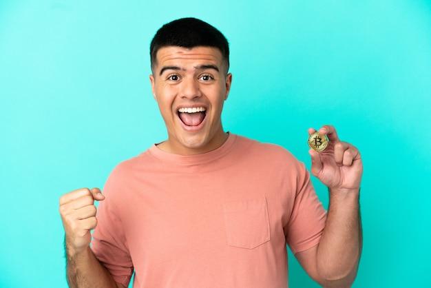Młody przystojny mężczyzna trzymający bitcoina na odosobnionym niebieskim tle świętujący zwycięstwo w pozycji zwycięzcy