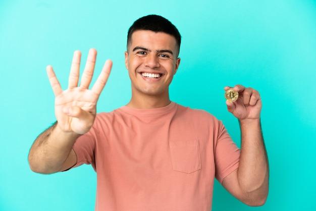 Młody przystojny mężczyzna trzymający bitcoina na odosobnionym niebieskim tle szczęśliwy i liczący cztery palcami