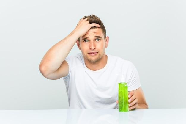 Młody przystojny mężczyzna trzymający butelkę aloesu, będąc w szoku, przypomniał sobie ważne spotkanie.