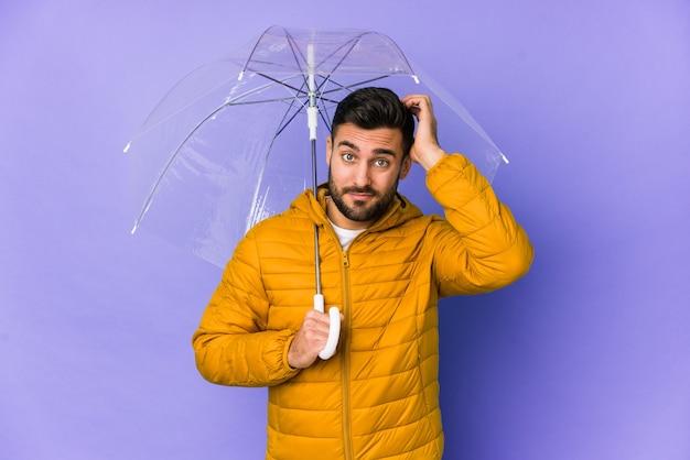 Młody przystojny mężczyzna trzymający parasol na białym tle będąc w szoku, przypomniała sobie ważne spotkanie.