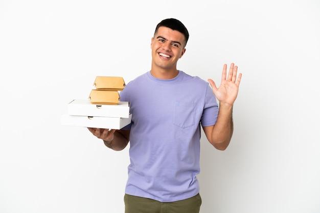 Młody przystojny mężczyzna trzymający pizze i hamburgery na białym tle, pozdrawiając ręką ze szczęśliwym wyrazem twarzy