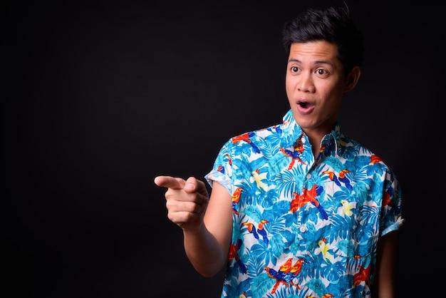 Młody przystojny mężczyzna turystyczny filipino gotowy na wakacje na czarnej ścianie