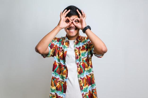 Młody przystojny mężczyzna ubrany dorywczo koszula robi ok gest jak lornetka wystaje język, oczy patrząc przez palce. szalona ekspresja na białym tle