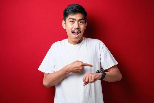 Młody przystojny mężczyzna ubrany w białą koszulkę stojącą na odosobnionym czerwonym tle w pośpiechu wskazując na czas, niecierpliwość, zdenerwowanie i złość na opóźnienie terminu