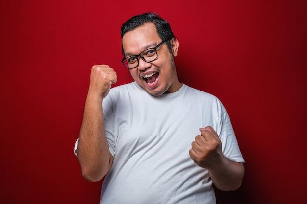 Młody przystojny mężczyzna ubrany w biały t-shirt stojący na białym tle czerwony bardzo szczęśliwy i podekscytowany robi gest zwycięzcy z podniesionymi rękami, uśmiechając się i krzycząc o sukces. koncepcja uroczystości