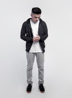 Młody przystojny mężczyzna ubrany w czarną bluzę z kapturem i białą koszulkę na białym tle na tle