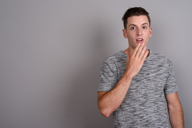 Młody przystojny mężczyzna ubrany w szarą koszulę na szaro