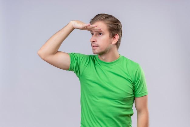 Młody przystojny mężczyzna ubrany w zielony t-shirt patrząc daleko