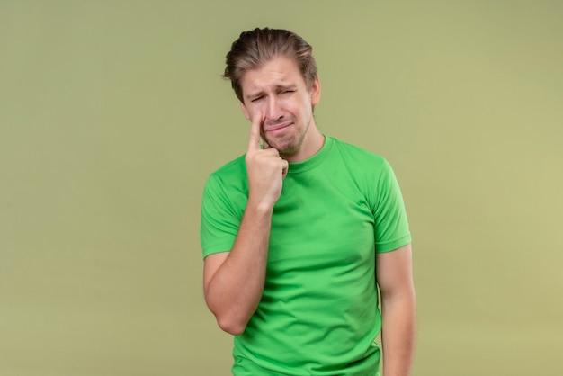 Młody przystojny mężczyzna ubrany w zielony t-shirt płacze ze smutnym wyrazem twarzy stojącej nad zieloną ścianą