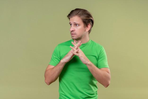Młody przystojny mężczyzna ubrany w zielony t-shirt trzymając się za ręce razem patrząc na bok ze smutnym wyrazem twarzy stojącej na zielonej ścianie