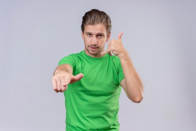 Młody przystojny mężczyzna ubrany w zielony t-shirt, wskazując do przodu i wykonywania gestu połączenia