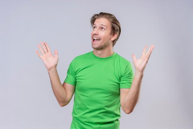 Młody przystojny mężczyzna ubrany w zielony t-shirt