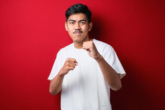 Młody przystojny mężczyzna ubrany w zwykłą koszulę stojący na czerwonym tle uderzający pięścią w walkę, agresywny i wściekły atak, groźba i przemoc