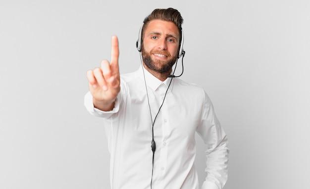 Młody przystojny mężczyzna uśmiecha się dumnie i pewnie co numer jeden. koncepcja telemarketingu