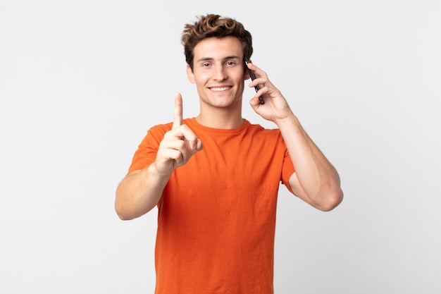 Młody przystojny mężczyzna uśmiecha się dumnie i pewnie robi numer jeden i rozmawia ze smartfonem